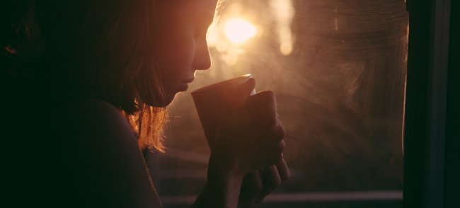 woman at sundawn with a mug - freelance writing guide